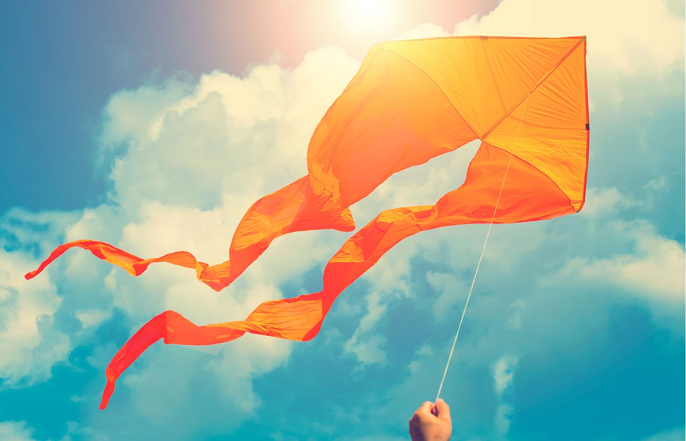 Flying orange kite on a sunny day