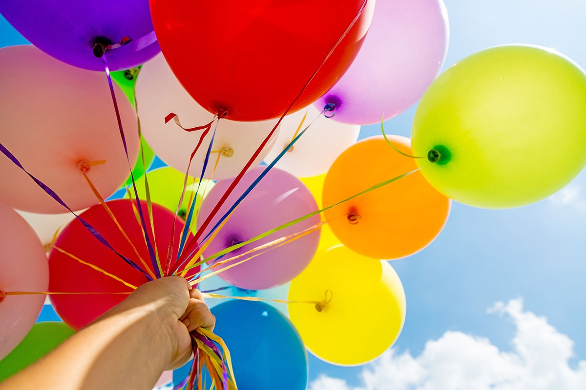 holding balloons on a sunny day
