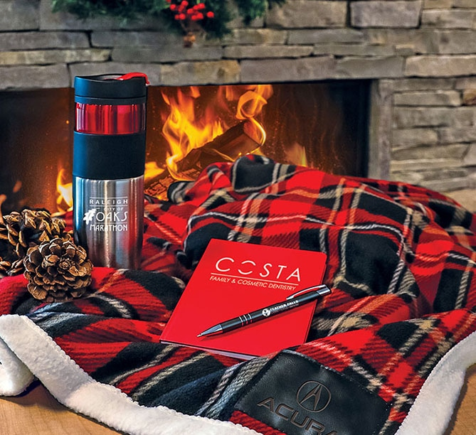 Holiday gifts grouping of tumbler, notebook, pen, and plaid blanket