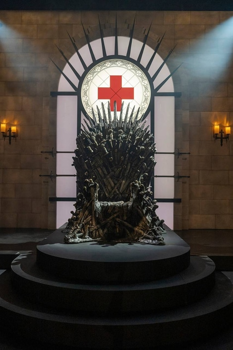 Iron Throne made from a multitude of swords, with a stained glass image of the American Red Cross logo above its back
