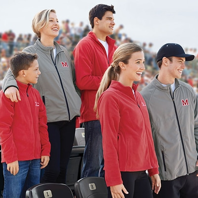 Sport fans standing in bleachers wearing fleece jackets customized with team logo