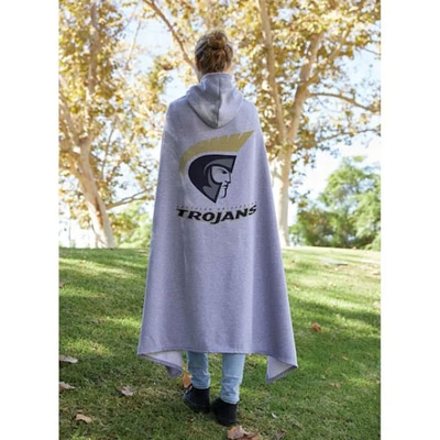 Woman standing in green grass wearing a grey hooded sweatshirt blanket with a large logo