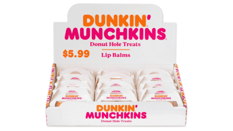 Twelve Dunkin lip balms in a white display box with orange and pink text