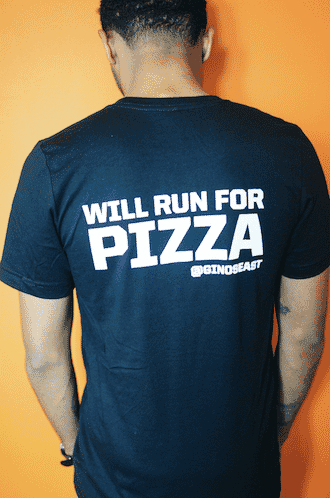 Black t-shirt with white text that reads 'Will run for pizza' and the Gino's East social media handle
