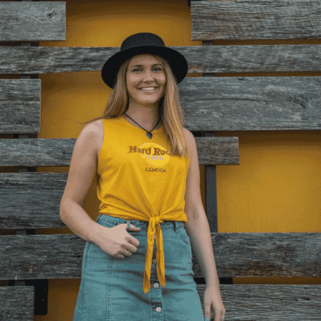 Woman wearing a yellow Hard Rock Cafe London t-shirt against a wooden backdrop