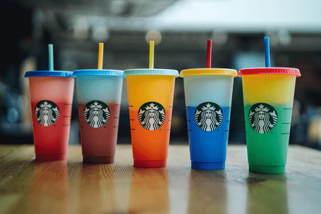 Five Starbucks color-changing cups in various colors on a wooden tabletop