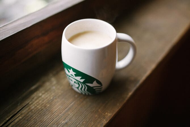 White mug with green Starbucks logo on brown wooden counter
