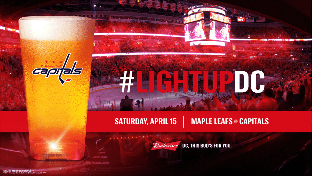 Beer glass with red light-up base in front of a crowded hockey stadium, with the hashtag 'light up DC'