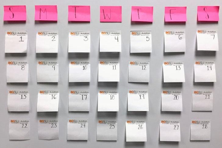 Sticky note calendar on white board