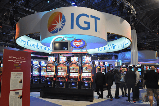 Large booth for the company International Game Technology (IGT) with several lit-up slot machines