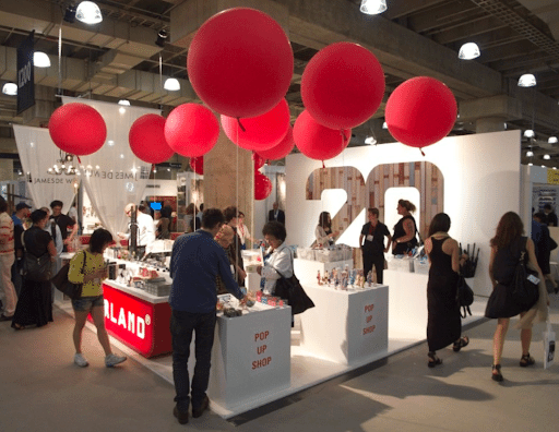 Pop-up shop booth for the brand Kikkerland decorated with large red balloons