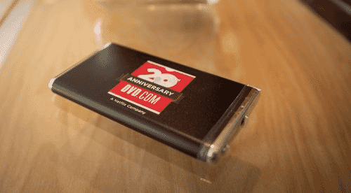 Black, red and silver Netflix-branded power bank on brown wooden table