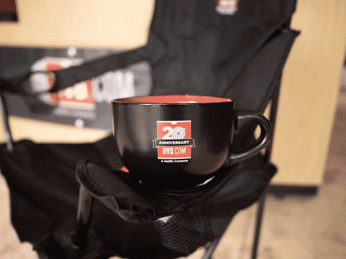 Red and black Netflix-branded mug sitting on the arm of a black camping chair