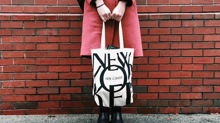 Woman in pink coat holding a New Yorker tote bag in front of a red brick wall