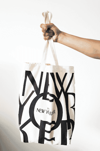 Woman's hand holding a New Yorker tote bag in front of a white wall
