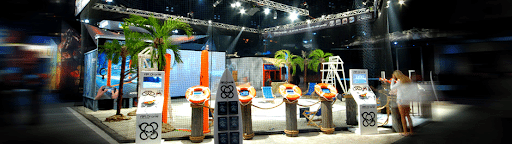 Beach-themed booth for the company Parrot decorated with lifebuoys and palm trees