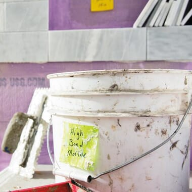 Dirty plastic bucket in a construction site labeled with a Post-it Extreme Sticky Note