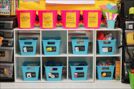 Plastic bins of school supplies in an elementary school classroom labeled with Post-it Extreme Sticky Notes
