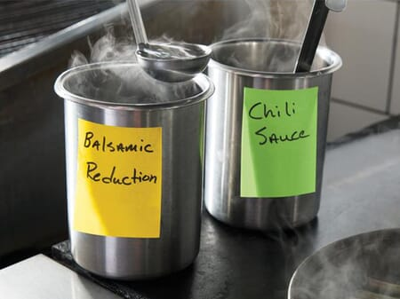 Two steaming stainless steel pots in an industrial kitchen, each labeled with a Post-it Extreme Sticky Note