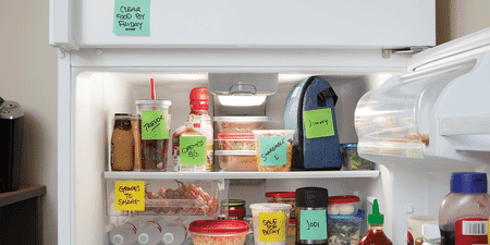 Various food containers in an office fridge, each labeled with a Post-it Extreme Sticky Note