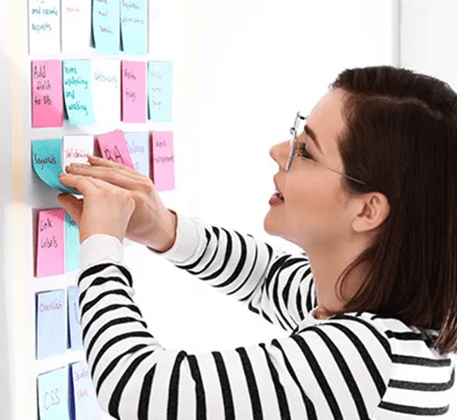 employee using sticky notes on a white board