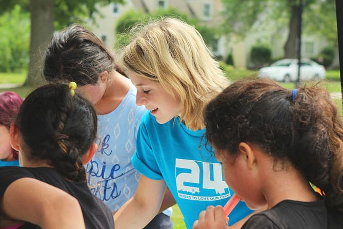 Woman in blue t-shirt talking with a group of children on a green grassy lawn