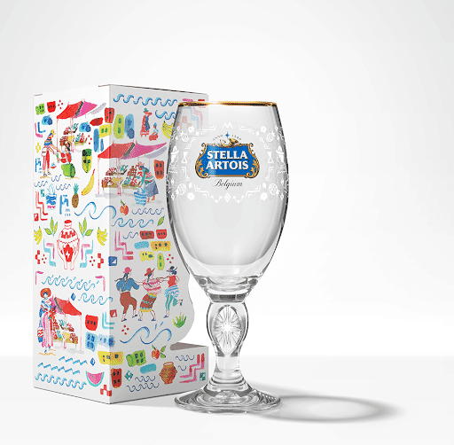 Clear glass Stella Artois-branded chalice with gold rim and blue logo next to colorful gift box