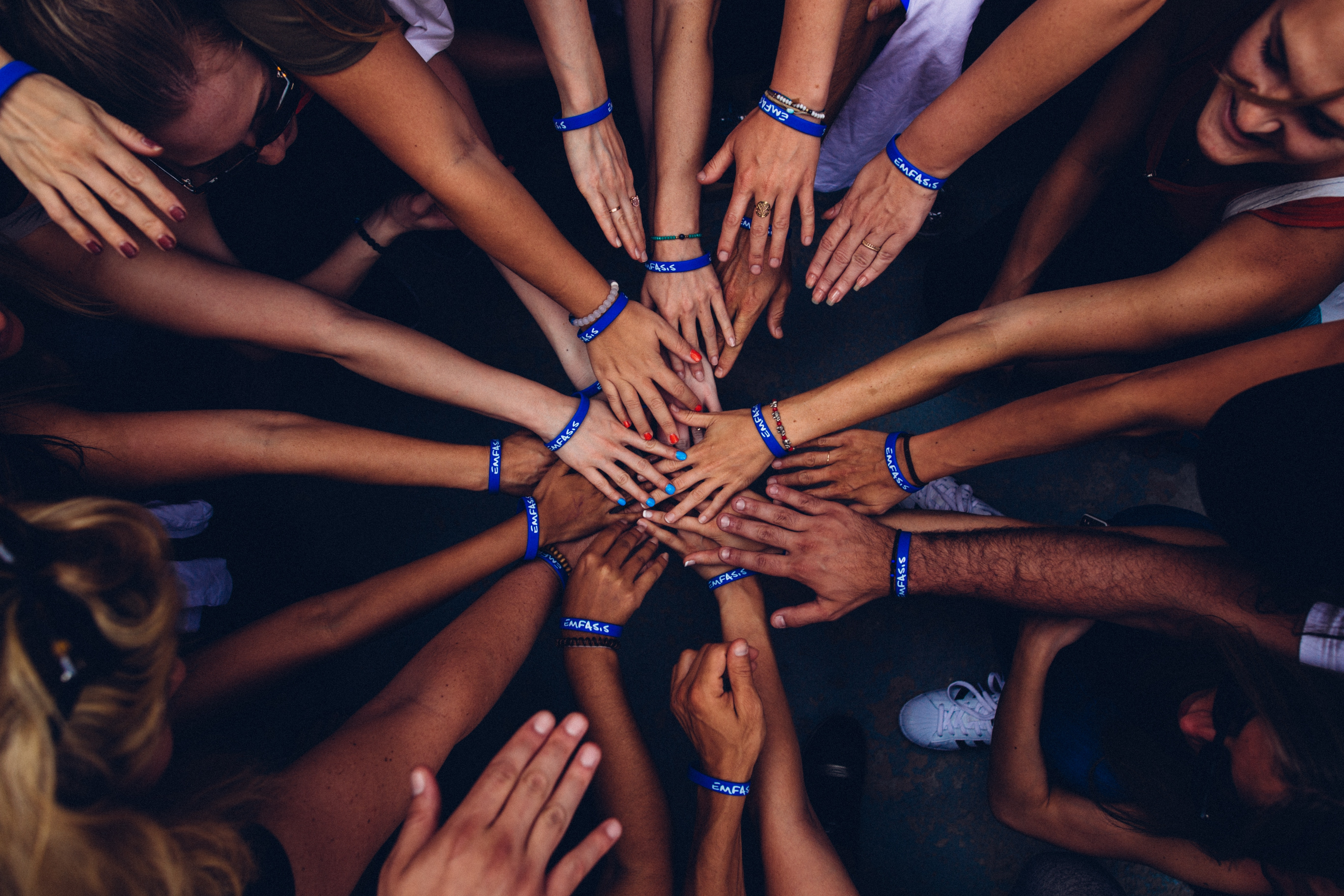 Aerial view of group of people standing in a circle wearing blue silicone bracelets putting their hands together