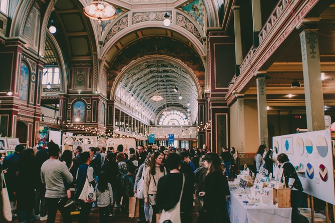 Crowd of people looking at booths in a large and ornate trade show hall.