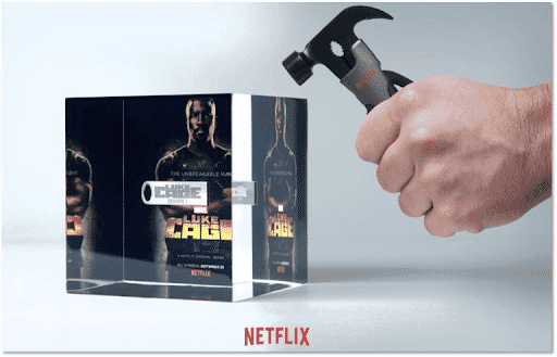 Man's hand holding hammer above clear Luke Cage-branded cube containing a USB drive