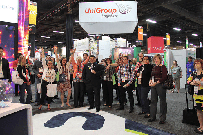 Crowd of people cheering at a trade show booth for the company UniGroup Logistics