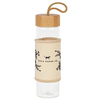 Clear glass water bottle with beige canvas sleeve, black logo and bamboo lid