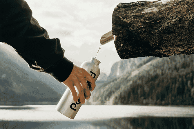 Man holding stainless steel tumbler with black logo in front of a lake and mountains