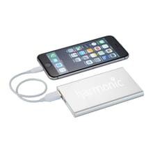 Small rose gold power bank with white logo and white cord running to black iPhone